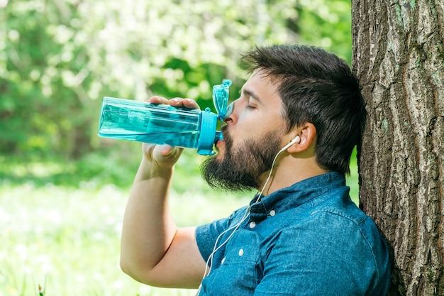 Feche o retrato de um homem beber água de uma garrafa fora