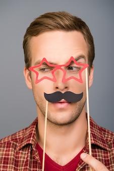 Feche o retrato de um homem cômico com bigode de papel e óculos como estrelas