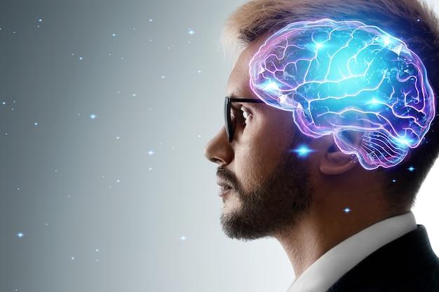 Feche o retrato de um homem de perfil e um holograma de um cérebro em funcionamento. o conceito de inteligência, trabalho do cérebro, processo de pensamento.