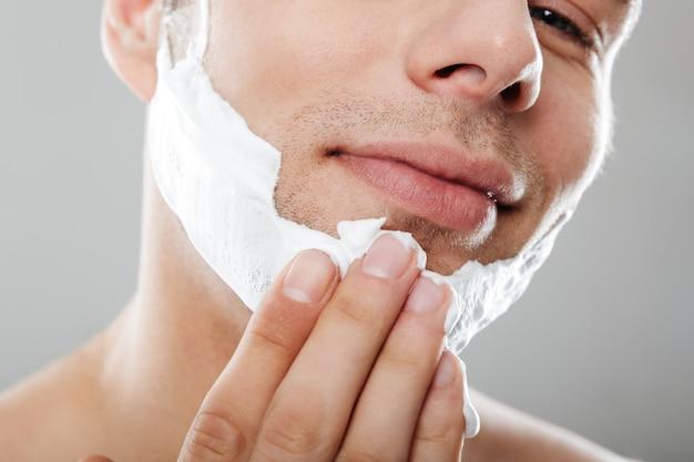 Feche o retrato de um homem feliz, aplicando espuma de barbear
