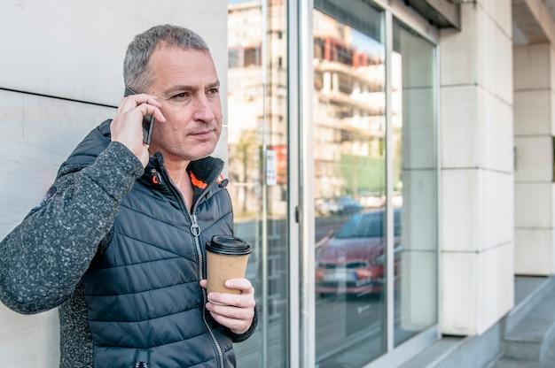 Feche o retrato de um homem maduro feliz falando no celular e sorrindo. retrato de um homem em uma conversa por telefone celular.
