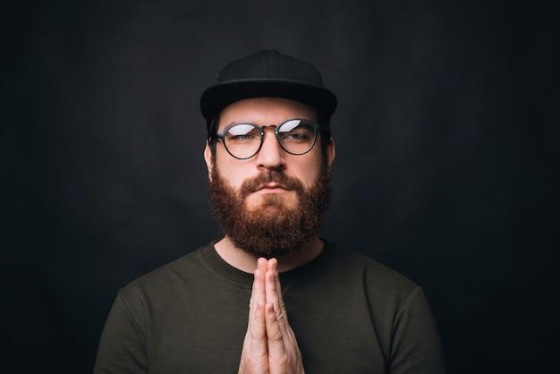 Feche o retrato de um homem sério, juntos de mãos dadas, rezando com os olhos abertos.