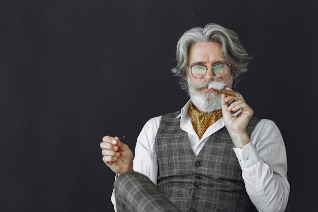 Feche o retrato de um homem sorridente à moda antiga. avô com um charuto e uísque.
