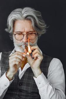 Feche o retrato de um homem sorridente à moda antiga. avô com um charuto.