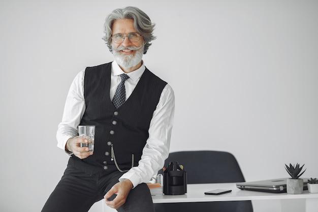 Feche o retrato de um homem sorridente à moda antiga. avô com um copo d'água.