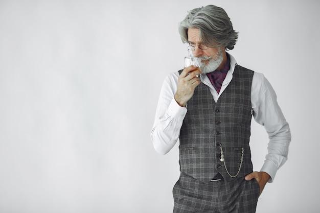 Feche o retrato de um homem sorridente à moda antiga. avô com um copo de uísque.