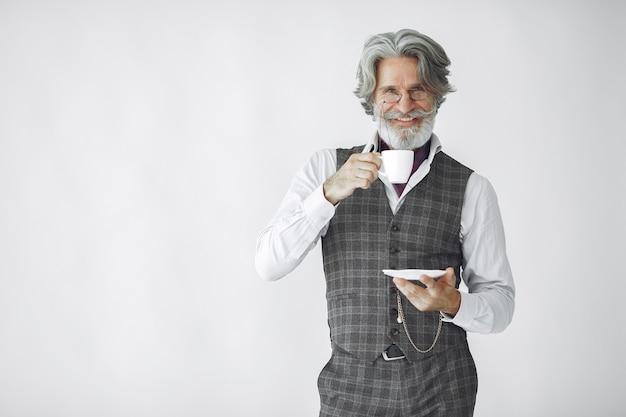 Feche o retrato de um homem sorridente à moda antiga. avô com uma caneca de chá.