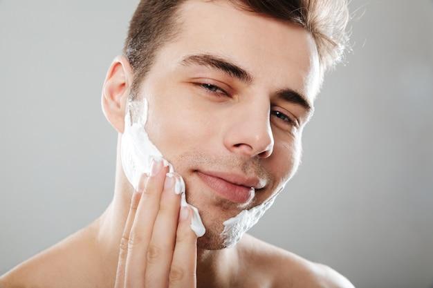 Feche o retrato de um homem sorridente, aplicando espuma de barbear