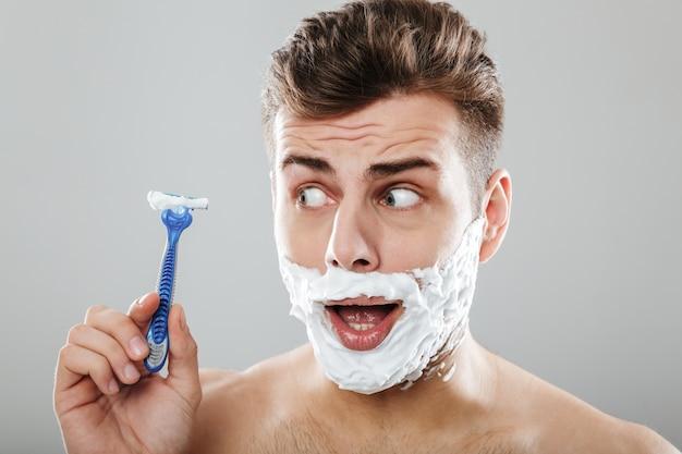 Feche o retrato de um homem sorridente com espuma de barbear