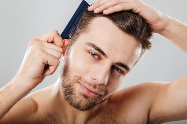 Feche o retrato de um homem sorridente, penteando o cabelo