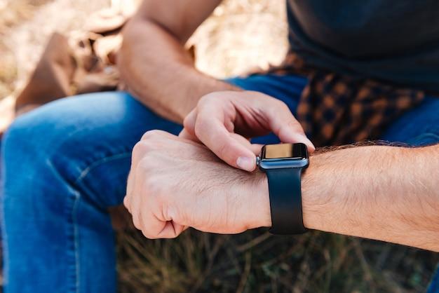 Feche o retrato de um homem usando smartwatch enquanto está sentado ao ar livre