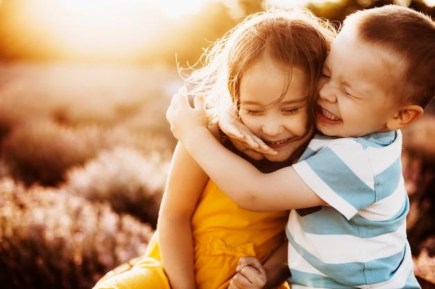 Feche o retrato de um irmão mais novo e uma irmã abraçando com os olhos fechados, rindo contra o pôr do sol em um campo de lavanda.