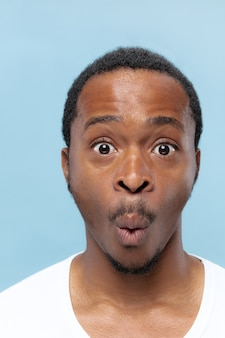 Feche o retrato de um jovem afro-americano em uma camisa branca na parede azul. emoções humanas, expressão facial, anúncio, conceito de vendas. parece chocado, surpreso, maravilhado.