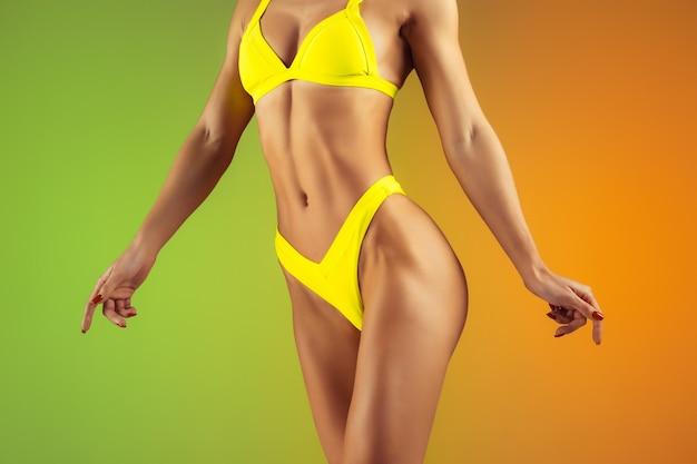 Feche o retrato de um jovem apto e esportiva mulher caucasiana em elegantes trajes de banho amarelos na parede gradiente. lindo modelo bem cuidado. corpo perfeito para o verão. beleza, resort, conceito de esporte.