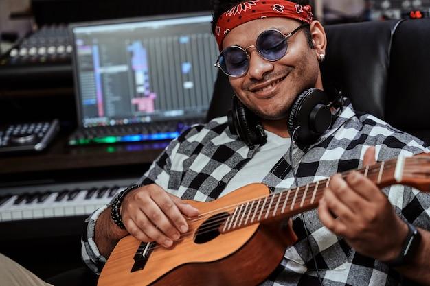 Feche o retrato de um jovem artista masculino feliz em óculos de sol, sorrindo enquanto toca cavaquinho