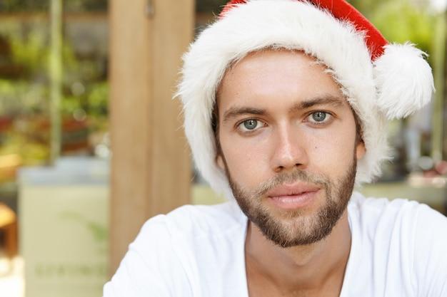 Feche o retrato de um jovem atraente caucasiano vestindo camiseta casual e chapéu de papai noel, olhando para a câmera com um sorriso confiante, passando um bom tempo no café