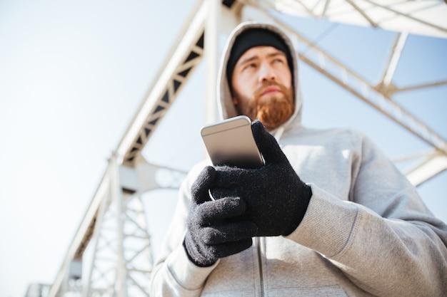 Feche o retrato de um jovem barbudo com capuz em pé na ponte urbana com um telefone celular