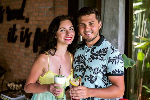 Feche o retrato de um jovem casal bonito feliz fazendo vivas na câmera, clima de festa tropical, se divertindo juntos, posando no café, relaxar no verão.