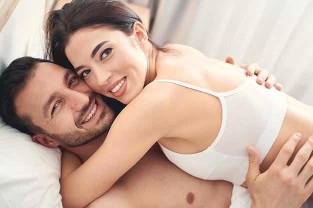 Feche o retrato de um jovem casal sorridente e feliz se abraçando na cama