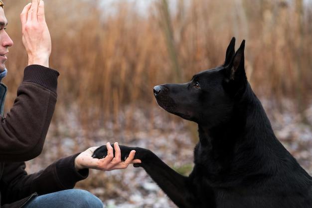 Feche o retrato de um jovem elegante caucasiano treinando com um grande cachorro preto ao ar livre