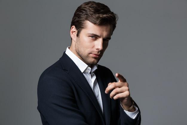 Feche o retrato de um jovem empresário bonito vestido com um terno isolado sobre uma parede cinza, apontando o dedo
