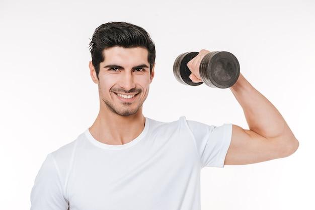 Feche o retrato de um jovem fisiculturista sorridente segurando halteres pesados isolados em um fundo branco