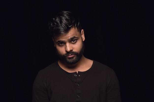 Feche o retrato de um jovem hindu isolado na parede preta do estúdio
