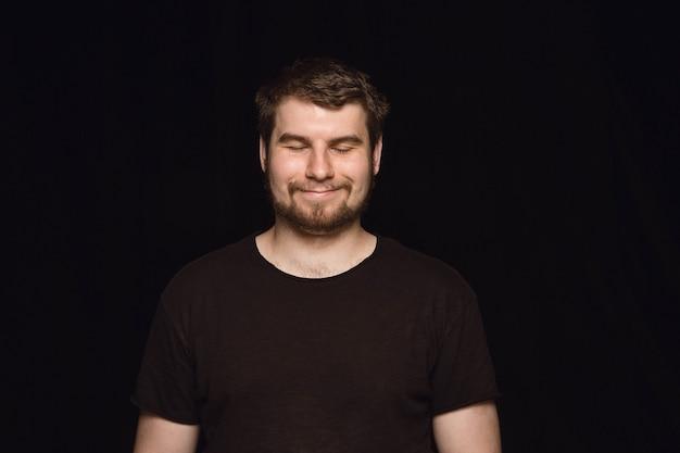 Feche o retrato de um jovem isolado na parede preta do estúdio