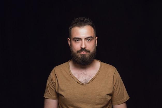 Feche o retrato de um jovem isolado no estúdio preto