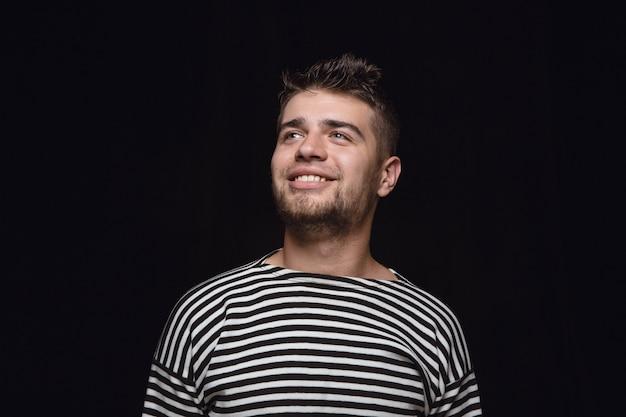 Feche o retrato de um jovem isolado no fundo preto do estúdio. photoshot de emoções reais do modelo masculino. sonhando e sorrindo, esperançoso e feliz. expressão facial, conceito de emoções humanas.