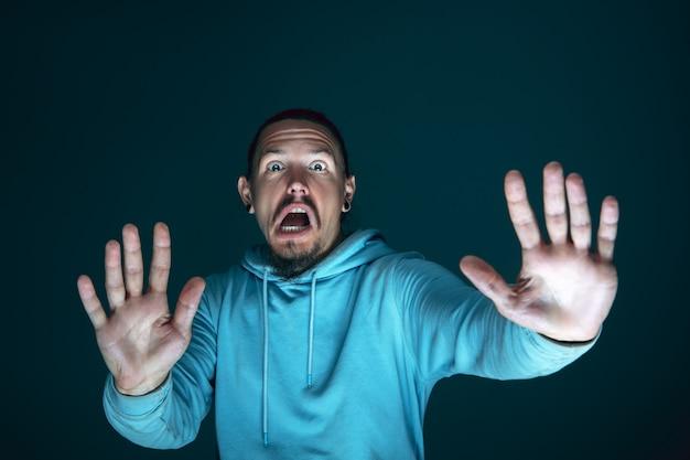 Feche o retrato de um jovem louco com medo e chocado homem caucasiano isolado em fundo escuro.