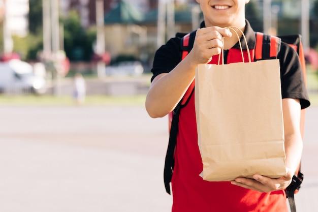 Feche o retrato de um jovem positivo, serviço de entrega de pessoa de mensageiro de porta em porta, entrega feliz
