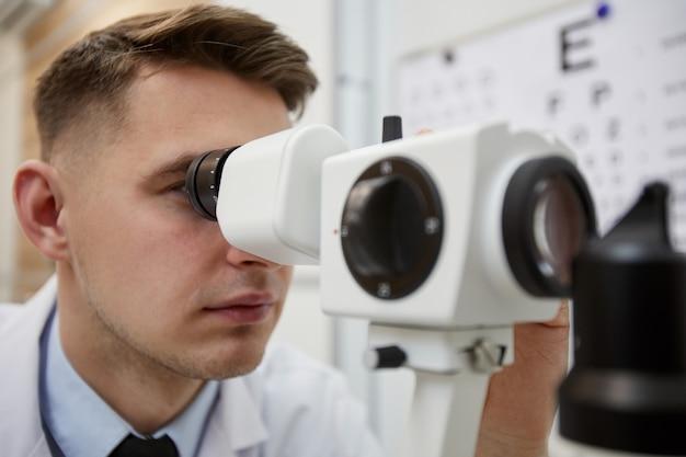 Feche o retrato de um optometrista usando uma máquina de refratômetro