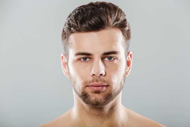Feche o retrato de um rosto jovem barbudo