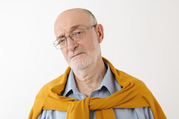 Feche o retrato de um sênior caucasiano barbudo e carrancudo, com a cabeça careca posando usando óculos e roupas elegantes, com expressão facial triste e descontente