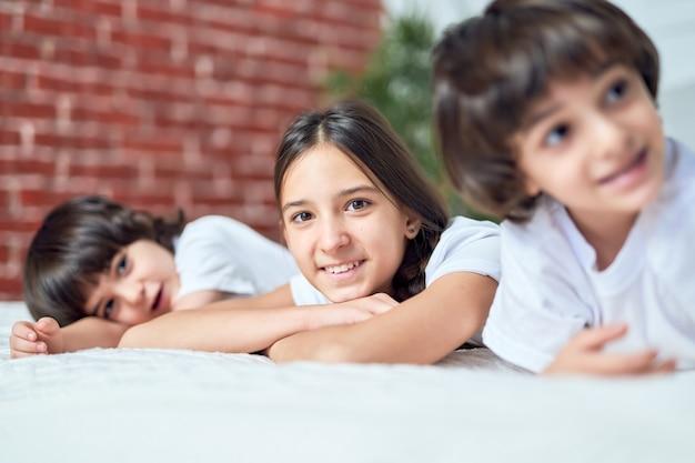 Feche o retrato de uma adolescente latina sorrindo para a câmera. irmã passando um tempo com seus dois irmãos mais novos, deitada na cama em casa. conceito de infância feliz