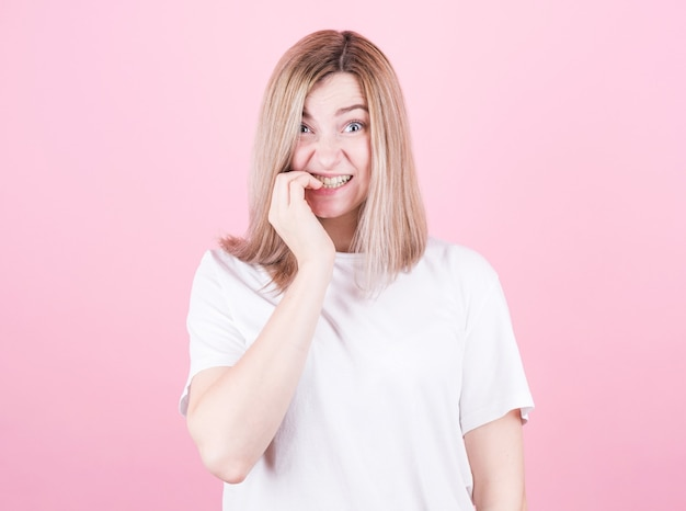 Feche o retrato de uma adolescente preocupada em uma camiseta branca roendo as unhas isoladas sobre fundo rosa