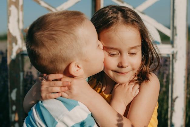 Feche o retrato de uma adorável criança, abraçando e beijando sua irmã ao ar livre no pôr do sol.