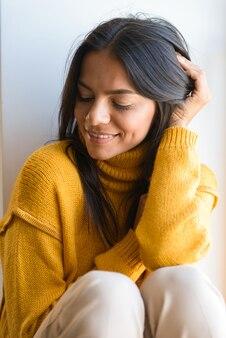 Feche o retrato de uma adorável jovem sorridente, vestida de suéter, sentada na janela dentro de casa, de olhos fechados