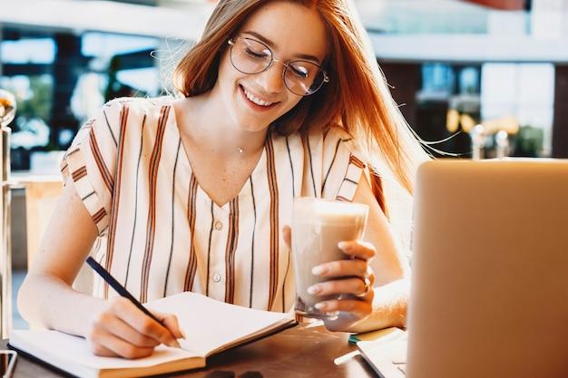 Feche o retrato de uma adorável jovem tomando notas enquanto trabalha como freelancer em um café