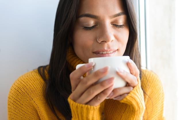 Feche o retrato de uma adorável jovem vestida com um suéter, sentada na janela dentro de casa, bebendo uma xícara de chá