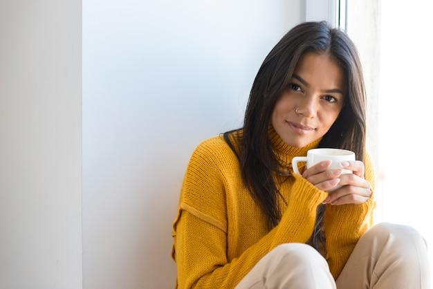 Feche o retrato de uma adorável jovem vestida com um suéter, sentada na janela dentro de casa, segurando uma xícara de chá