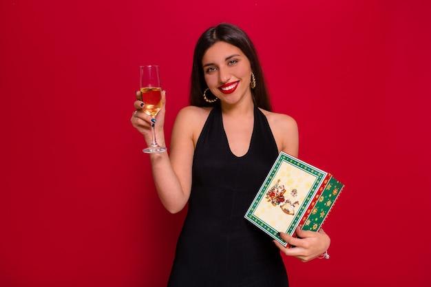 Feche o retrato de uma adorável mulher sorridente com cabelo escuro e lábios vermelhos, segurando uma taça de champanhe e um presente de natal posando sobre uma parede vermelha