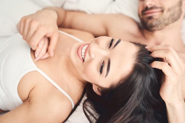 Feche o retrato de uma adorável senhora sorridente em roupa íntima deitada sobre o peito de um homem barbudo