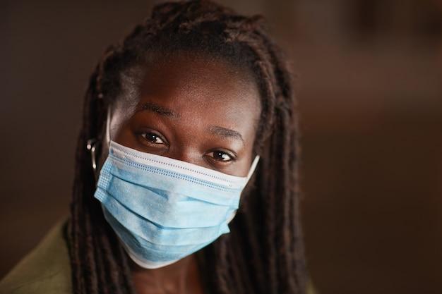 Feche o retrato de uma alegre mulher afro-americana usando máscara e olhando para a câmera contra um fundo escuro, copie o espaço