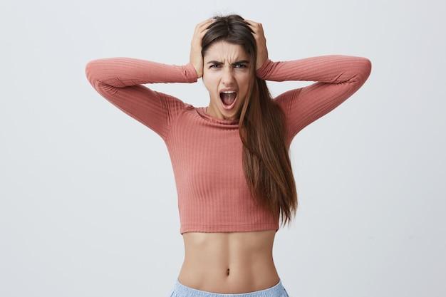 Feche o retrato de uma atraente jovem mulher caucasiana expressiva com cabelos longos escuros na bermuda rosa e azul, apertando a cabeça com as mãos com expressão de raiva, gritando alto.