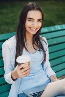Feche o retrato de uma bela jovem com cabelo escuro, sorrindo, segurando uma xícara de café e um laptop com as pernas, sentado em um banco do lado de fora.