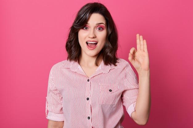 Feche o retrato de uma bela jovem de cabelos escuros, vestindo camisa listrada, mostrando sinal de mão okey