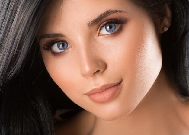 Feche o retrato de uma bela jovem de olhos azuis. conceito de cuidados com a pele.