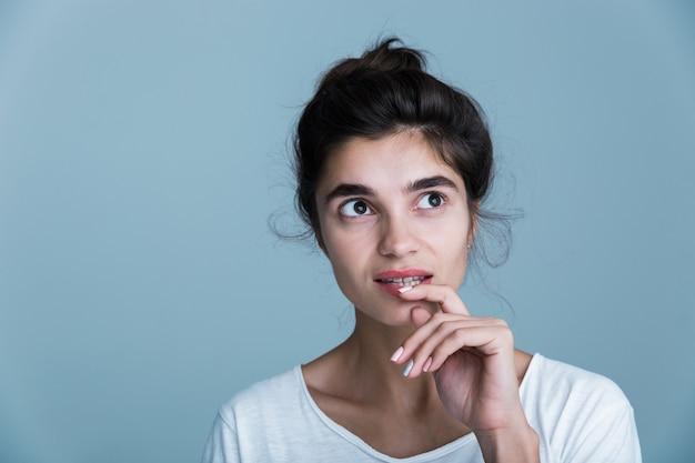 Feche o retrato de uma bela jovem morena vestindo uma camiseta branca em pé, isolado sobre um fundo azul, posando, tocando o rosto